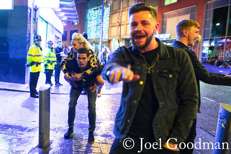 "© Joel Goodman - 07973 332324 . 17/12/2016 . Manchester , UK . A man carries a woman on his back along Withy Grove . Revellers out in Manchester City Centre overnight during "" Mad Friday "" , named for being one of the busiest nights of the year for the emergency services in the UK . Photo credit : Joel Goodman"