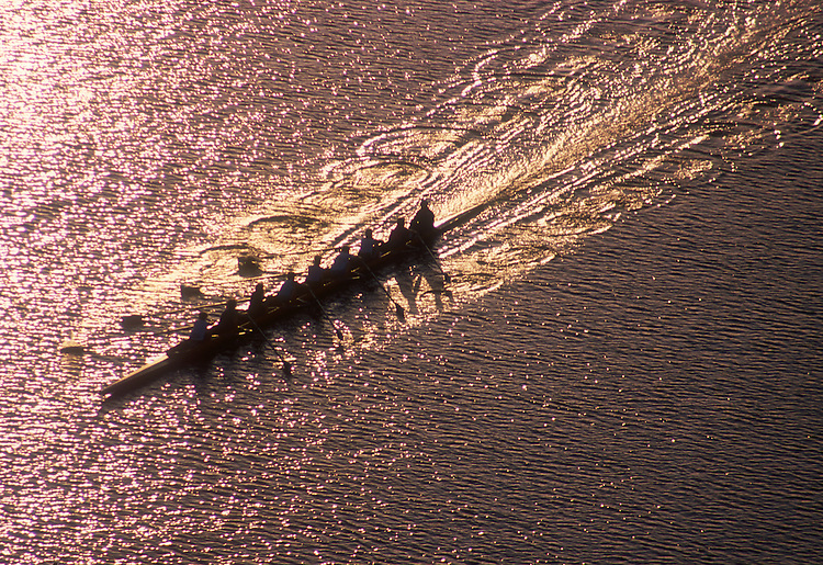 Rowing, women's eight oared shell from above and the side, wake and oar puddles streaming aft,