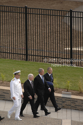 Arlington, VA - September 11, 2008 -- The official party, from left to right: Chairman, Joint Chiefs of Staff Michael Mullen; Secretary of Defense Robert Gates; United States President George W. Bush; and former Secretary of Defense Donald Rumsfeld walk back carrying a memorial cover after watching 184 joint service troops unveil the Pentagon Memorial Sept. 11, 2008. The national memorial is the first to be dedicated to those killed at the Pentagon on Sept. 11, 2001. The site contains 184 inscribed memorial units honoring the 59 people aboard American Airlines Flight 77 and the 125 in the building who lost their lives that day. .Credit: Jennifer Villalovos - DoD via CNP