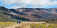 Two male hikers viewing the Sliding Sands trail and visitor center from inside the crater in HALEAKALA NATIONAL PARK on Maui in Hawaii USA