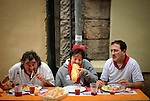 People eat lunch on the street during the San Fermin festival, on July 10, 2012, in the Northern Spanish city of Pamplona. The festival is a symbol of Spanish culture that attracts thousands of tourists to watch the bull runs despite heavy condemnation from animal rights groups. (c) Pedro ARMESTRE
