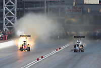 Mar. 31, 2012; Las Vegas, NV, USA: NHRA top fuel dragster driver Damien Harris (left) has an engine fire alongside Doug Kalitta during qualifying for the Summitracing.com Nationals at The Strip in Las Vegas. Mandatory Credit: Mark J. Rebilas-