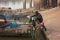 A fisherman prepares cormorants for fishing at dawn in Poyang county at Poyang Lake, Jiangxi Province, December 2014. Poyang Lake, located in the north of Jiangxi Province, is the largest freshwater lake in China. It fluctuates dramatically between wet and dry seasons, from 3,500 square kilometres down to about 200 square kilometres. The lake provides a habitat for half a million migratory birds.