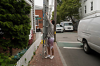 Alex Almonfrey, 25, cleans windows on the Jack Wills storefront in Edgartown, Martha's Vineyard, Massachusetts, USA. Almonfrey said he worked on temporary visas in previous years but is now staying in the US permanently. He works primarily as a painter, but also does odd jobs like this window cleaning.