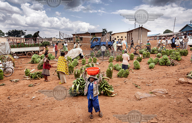 A young boy carries a basin of peppers on his head at a market where hands of bananas are laid out for sale.