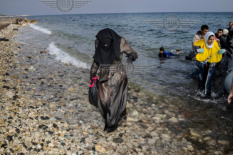 A refugee woman in a niqab walks off a boat that carried her and tens of other refugees from the Turkish coast six hours earlier.