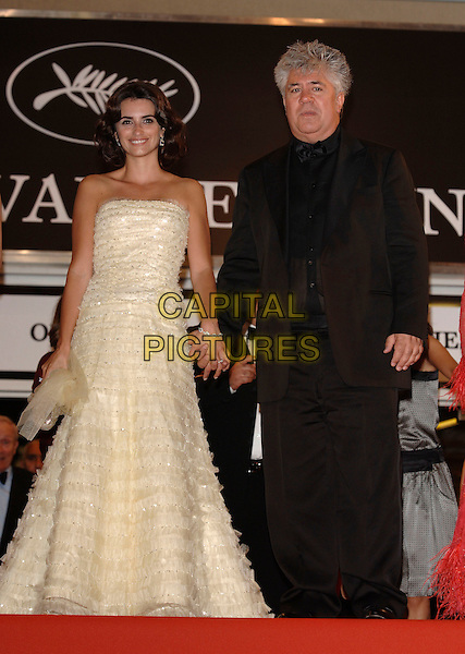 "PENELOPE CRUZ & PEDRO ALMODOVAR.""Volver"" screening arrivals.59th International Cannes Film Festival, France.19th May 2006.Ref: PL.full length black suit white strapless ruffle gown dress holding hands.www.capitalpictures.com.sales@capitalpictures.com.©Phil Loftus/Capital Pictures"