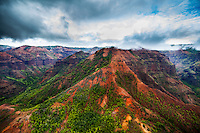 Red dirt and green trees provide dramatic color in aerial shot of Waimea Canyon on Kaua'i.