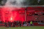 Away supporters celebrate their team's goal by setting a flare alight at Broadhurst Park, Manchester, the new home of FC United of Manchester during the club's match against Benfica, champions of Portugal, which marked the official opening of their new stadium. FC United Manchester were formed in 2005 by fans disillusioned by the takeover of Manchester United by the Glazer family from America. The club gained several promotions and played in National League North in the 2015-16 season, but lost this match 1-0.