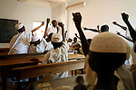 Darfuri children rush to answer a teacher's question in their 800 capacity school in Klaimendo village in North Darfur, 04 Dec, 2008. Despite the fact that North Darfur is believed to currently have the highest concentration of NGOs in the world, the creation of Klaimendo district and village is the work of people born and raised in the area, rather than an outside aid agency. (John D McHugh)
