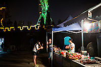 People buy coconuts to drink from near a replica of the Great Wall at Yangrenjie, or Meixin Foreigner Street, a sprawling amusement and oddity park in northeastern Chongqing, China. Park is popular among lower-class Chongqingers. Meat skewers cost 1RMB per skewer.