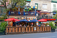 People sitting and talking outdoors at Restaurant Napoli pizzeria on Rue Saint Denis street, Latin Quarter, Montreal, Quebec, Canada