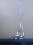 A sail boat sails past Alcatraz Island on San Francisco Bay, California.