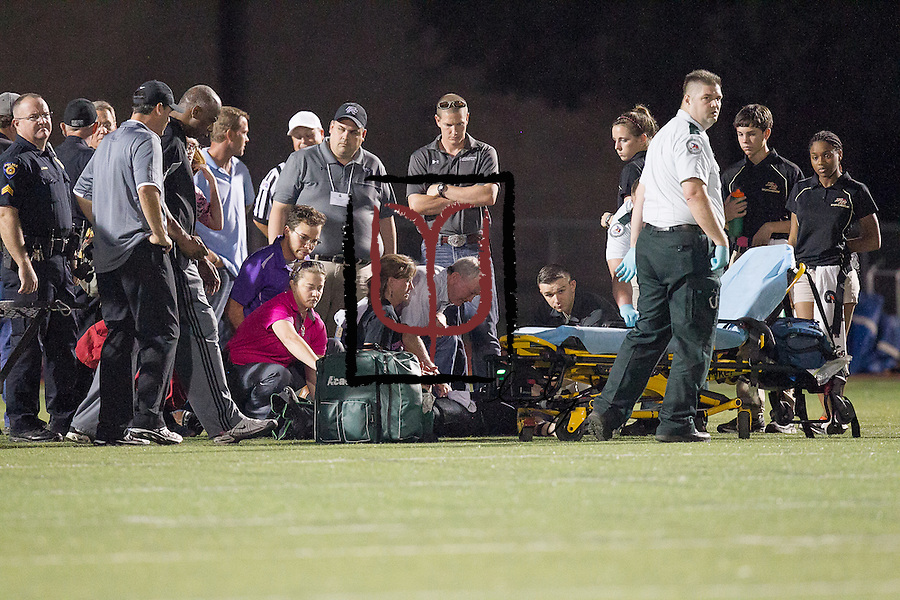 Surrounded by family, Cedar Ridge quarterback Travis Malesky gets medical attention in the first half against Rouse at Dragon Stadium.  (LOURDES M SHOAF for Round Rock Leader)