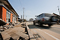 Mar. 13, 2011 - Kita-Ibaraki, Japan - A car drives past by a house in ruins two days after the 8.9 magnitude earthquake struck followed by a tsunami that hit the north-eastern region. The death toll is currently unknown with casualties that may run well into the thousands.