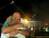 Pastor Ray Thompson hugs parishoner Sheila Mahoney as firefighers try to control a fire at the Mountain Creek Baptist Church Monday night. Several church members gathered along U.S. 29 to watch as firefighters tried in vain to save the building.