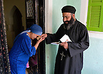 Father Joil Sobhe, a Coptic Orthodox priest, is greeted by a woman as he visits and blesses church members in the Egyptian village of Sakra.