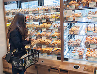A shopper buys baked goods in the new Whole Foods Market in opposite Bryant Park in New York on opening day Saturday, January 28, 2017. The store in Midtown Manhattan is the chain's 11th store to open in the city. The store has a large selection of prepared foods from a diverse group of vendors inside the store.  (© Richard B. Levine)
