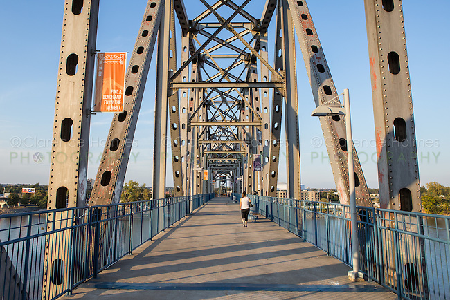 A woman walks on the walkway on the Junction Bridge on the Arkansas River Trail in Little Rock, Arkansas.