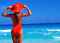 Young woman in orange swimsuit and large hat on beach
