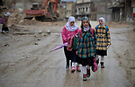 Girls walk along a muddy street as they make their way to school amid the rubble of the Old City of Mosul, Iraq, which was devastated during the 2017 Battle of Mosul, which led to the defeat of the Islamic State group, also known as ISIS. During control of the city by the Islamic State, most children didn't attend school.