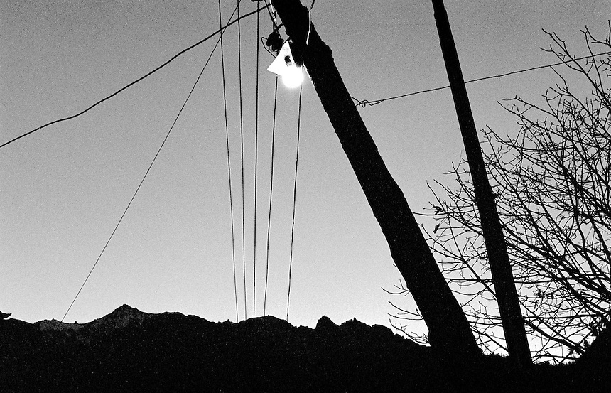 Light globe, powerlines and mountain ridge in the Annapurna Himal, Nepal, 2008. Photo: Ed Giles.