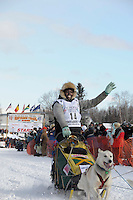Jamaican musher Newton Marshall waves to crowds during restart of Iditarod dogsled race from Willow, Alaska