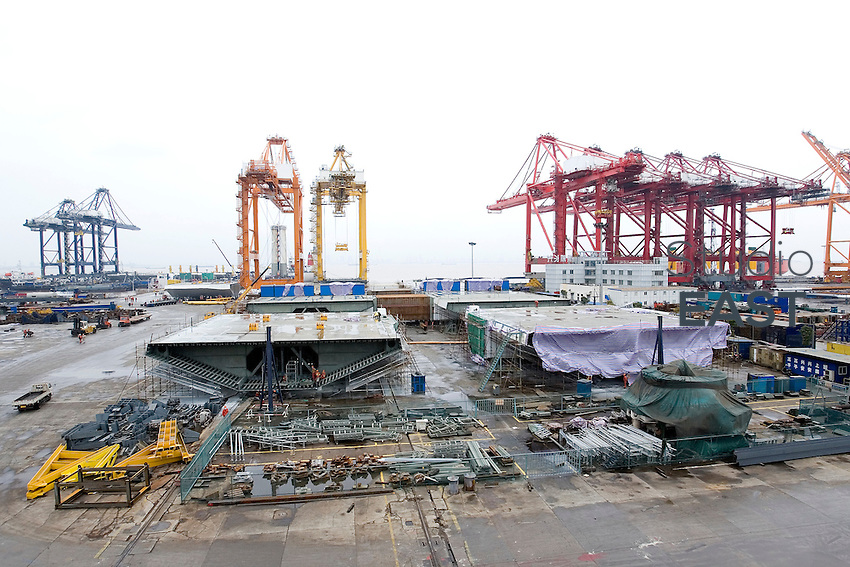 Completed OBGs are waiting or undergoing minor repairs, while in the background boat Zhenhua 17 waits on the pier for the loading of the first steel shipment, outside the workshops of Shanghai Zhenhua Port Machinery Co. Ltd. (ZPMC), on Changxing Island, Shanghai, on December 13, 2009. Photo by Lucas Schifres/Pictobank