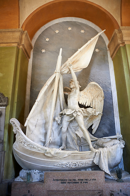 """Picture and image of the stone sculpture """"L'Angelo Nocchiero"""" (the Helmsman Angel). The sculpture depicts an angel, standing astride a small boat, beginning to secure the sails at the end of a journey. His garments are streaming behind him, suggesting a strong wind. The prow of the boat is the stoic face of a woman, and under the prow the water swirls. The Giacomo Carpaneto tomb  sculpted by Giovanni Scanzi in 1886. Section A, no 25, monumental tombs of the Staglieno Monumental Cemetery, Genoa, Italy"""