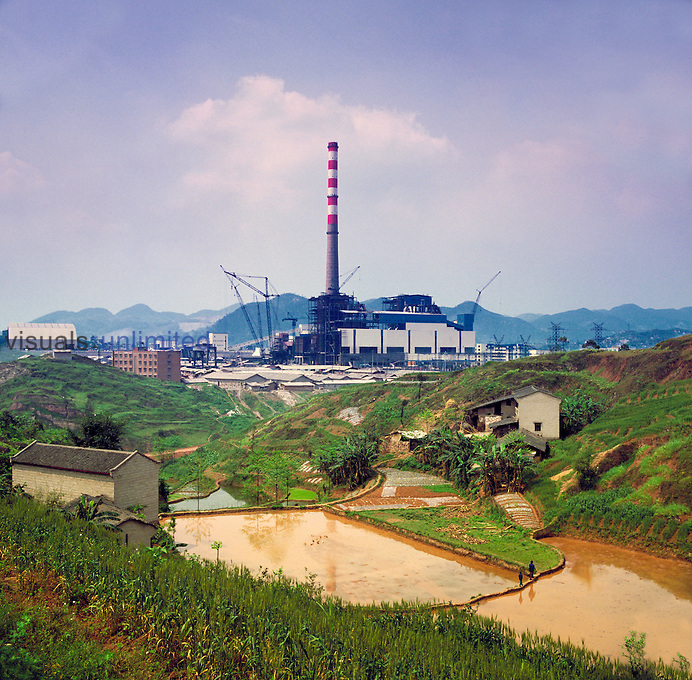 Power station on the Yangtse River under construction with a view over looking neighboring paddy fields, China.
