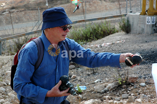 Foreign protestor carries tear gas canisters fired by Israeli troops during a demonstration against Israel's separation barrier in the West Bank village Bilin near Ramallah on Oct 9, 2009. Photo by Nedal Shtieh