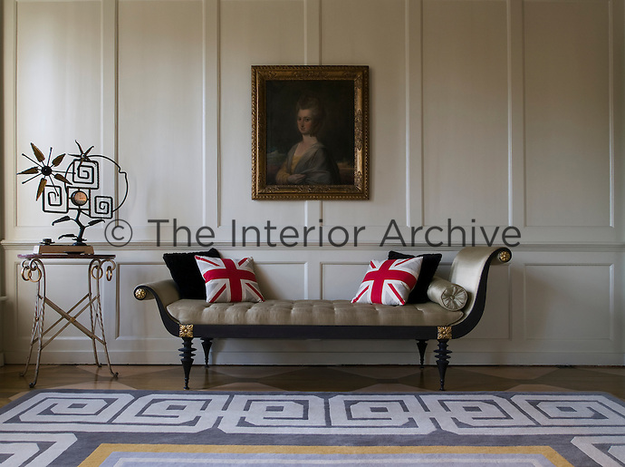A classical chaise-longue against the white wood panelling of the drawing room