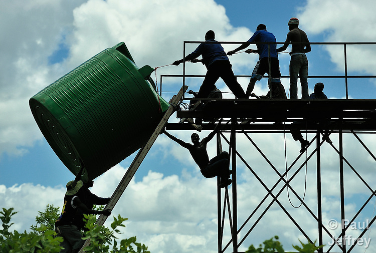"""Residents of Chisatha, a village in southern Malawi on its border with Mozambique, lift a 5,000 liter tank onto an elevated platform. Six such tanks will be placed on the platform, and then solar-powered pumps will fill them with water from a nearby river, providing villagers with irrigation water for their crops. The village has been hard hit by drought in recent years, leading to chronic food insecurity, especially during the """"hunger season,"""" when farmers are waiting for the harvest. The ACT Alliance, which is sponsoring the project, is working with farmers in the village to switch to alternative, drought-resistant crops, such as millet, as well as using irrigation and other improved techniques to increase agricultural yields."""