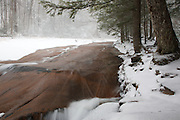 Franconia Notch State Park - Flume Brook in the Flume Gorge Scenic Area in Lincoln, New Hampshire USA during a snow storm.  Blowing snow can be seen