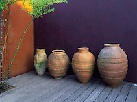 Row of terracotta pots/antique oil jars against aubergine rendered wall