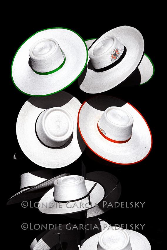 Rack of flat brimmed vaquero hats.