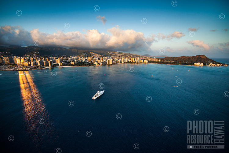 "The brilliant sun reflects perfectly off of the Hawai'i Prince Hotel and onto the ocean near a ""mega-yacht"" off the coast of Waikiki, with Diamond Head to the right, Honolulu, O'ahu."