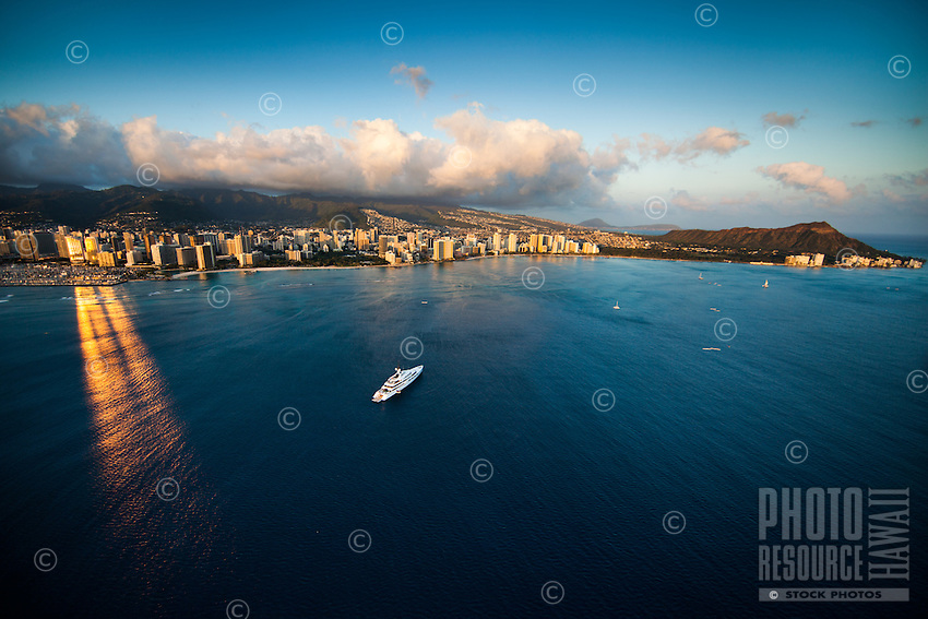 """The brilliant sun reflects perfectly off of the Hawai'i Prince Hotel and onto the ocean near a """"mega-yacht"""" off the coast of Waikiki, with Diamond Head to the right, Honolulu, O'ahu."""