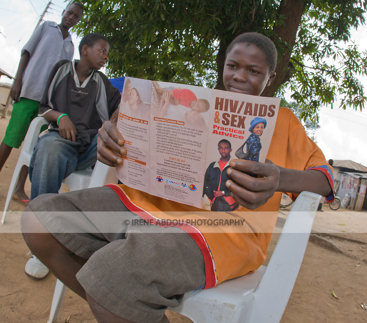 A teenager holds a brochure about HIV/AIDS and sex while listening to a behavior change communication session about HIV/AIDS prevention and transmission.  The brochure is distributed by the Society for Family Health, Nigeria's largest indigenous NGO and affiliate of the international NGO, Population Services INternational, with funding from the British Department for International Development (DFID) and the US Agency for International Development (USAID).
