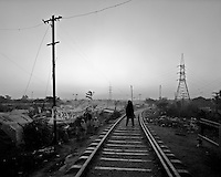 A man walks at dawn along the tracks that divide a camp of nomads who settled in the area a decade ago in the outskirts of Rawalpindi, Pakistan on Monday November 23 2009.