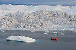 Tourist boat in front of large icebergs at midnight, end of June, mid summer night; Disko Bay, Greenland