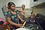 Vumila Masoka and Bashige Chichibanji, both refugees from the Democratic Republic of the Congo, cook a meal in the apartment of another Congolese refugee family in Durham , North Carolina. All were resettled with assistance from Church World Service, which resettles refugees in North Carolina and throughout the United States.<br /> <br /> <br /> Photo by Paul Jeffrey for Church World Service.