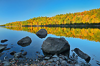 Autumn reflection on St. Nora Lake with rocky shoreline<br /> near Pine Springs<br /> Ontario<br /> Canada