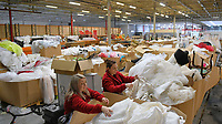 "Pictured: Staff members, Natasha Parfitt (left) and Michelle Curry, search through the wedding dresses in boxes at the John Pye Auctions warehouse in Pyle, south Wales, UK.<br /> Re: A bride cried tears of joy after her missing wedding dress was found among a pile of 20,000 gowns in a warehouse.<br /> Meg Stamp, 27, paid £1,300 for the beautiful ivory lace dress but it  was seized by liquidators after a bridal company went bust.<br /> It was boxed up along with 20,000 others and due to be sold for a knock-down price at auction.<br /> But determined Meg banged on the auctioneer door saying: ""I want my dress back"".<br /> Staff at John Pye auctioneers in Port Talbot spent three hours sifting through boxes until they finally found Meg's dream dress."