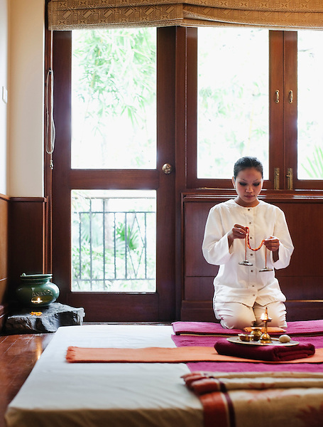A spa therapist at Ananda Spa prepares the Oriental I treatment room for a Thai Massage, Ananda in the Himalayas, The Palace Estate, Narendra Nagar, Tehri Garhwal, Uttarakhand, India. The Diya (or lamp) is filled with mustard oil and lit, and Tibetan chimes are rung to signify the beginning and end of a spa treatment.