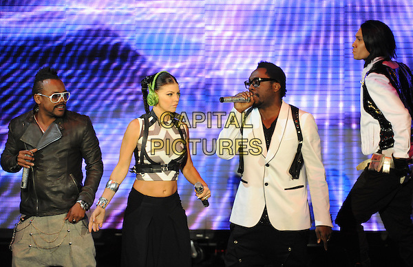 THE BLACK EYED PEAS - Apl.de.ap, Fergie, Will.i.am & Taboo  (Stacy Ann Ferguson).Live at The 102.7's KIIS-FM's Wango Tango 2009 held at The Verizon Wireless Ampitheatre in Irvine, California, USA..May 9th, 2009 .half length stacey stage concert live gig show performance music black cropped headphones earmuffs  top belly stomach midriff print green suspenders braces singing dancing profile white arm leather sunglasses shades .CAP/DVS.©Debbie VanStory/Capital Pictures.