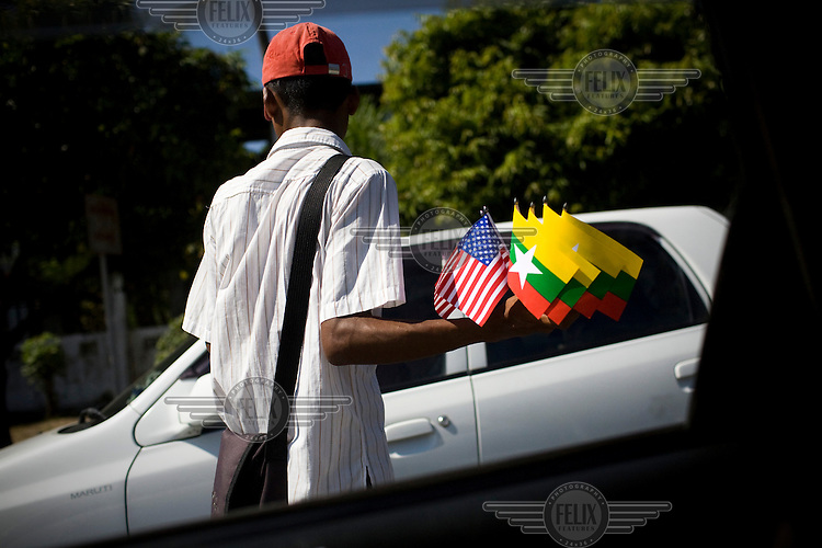 A street vendor sells small flags of the United States and the Burmese national flag on a street in Rangoon (Yangon). .