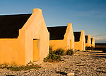 Bonaire, Netherland Antilles -- The yellow-painted slave huts at one of the several salt stations in the south of Bonaire (Orange Pan) seem to glow in the warm sunset light.