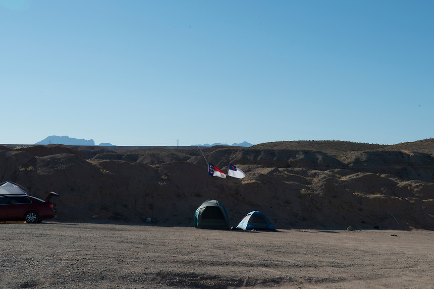 Two flags displaying the home-state and religious commitment of the supporters of Clive Bundy who came from all over the country to defend him from what they believe is a government overreach. The tents are in the militia camp &quot;liberty&quot; established near Bundy's ranch in Bunkerville, Nevada.<br /> The Bundy standoff is a 20-year legal dispute between the United States Bureau of Land Management (BLM) and cattle rancher Cliven Bundy in southeastern Nevada over unpaid grazing fees that eventually developed into an armed confrontation between protesters and law enforcement.