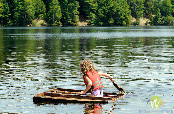 Ellie Works, age 6, playing on driftwood raft with driftwood paddle at Duck Cove.